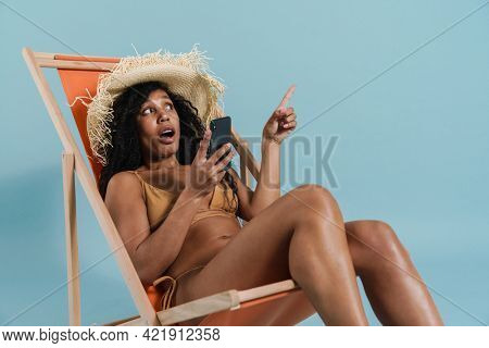 Black shocked woman using cellphone while sitting in chaise lounge isolated over blue background