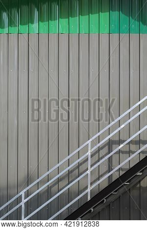 Metal Stair And Banister On Gray Corrugated Steel Wall With Green Roof Of Storehouse In Incomplete C