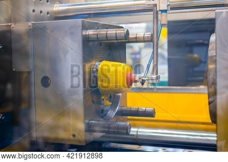 Injection Molding Machine With Robotic Arm During Work: Production Of Empty Polypropylene Yellow Cup