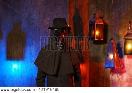 Portrait Of A Plague Doctor In A Black Leather Mask, Hat And Hood, Isolated Against A Dark Wall With