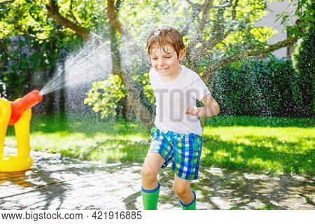 Funny Little Kid Boy Playing With A Garden Hose Sprinkler On Hot And Sunny Summer Day. Child Having