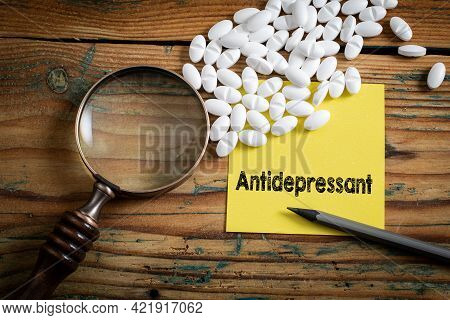 Antidepressant. Lot Of Pills And Magnifying Glass On A Wooden Table