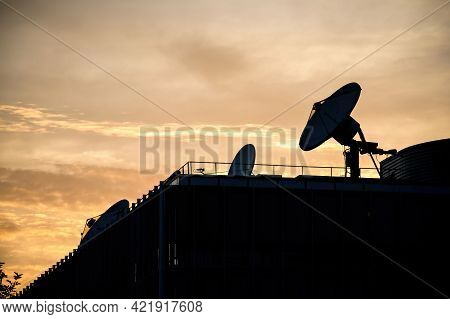 Yellow Sunset With Multiple Satellite Dishes Antenna On The Rooftop Of International Tv Station Tran