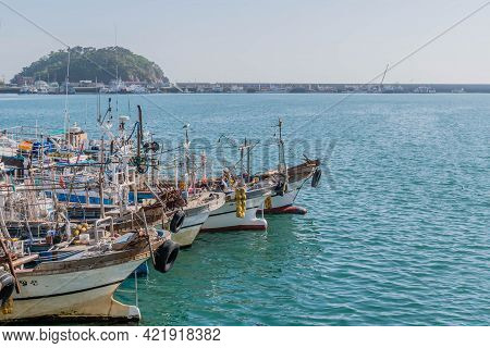 Sinjindo, South Korea; May 5, 2021: Fishing Trawlers Moored In Seaport Harbor On Overcast Day.