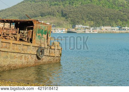 Sinjindo, South Korea; May 5, 2021: Side View Of Beached Old Rusty Barge With Stern Resting In Shall