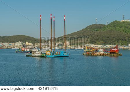 Sinjindo, South Korea; May 5, 2021: Barges With Industrial Cranes Working On Water In Small Seaport.