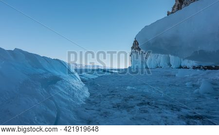 On The Frozen Lake There Are Blue Shiny Ice Hummocks. Icicles On A Frozen Rock Base. Clear Sky. Wint