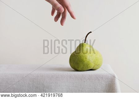 Pear On Table With Linen Tablecloth. Womans Hand Reaching For Pear. Summer Fruits Season. Copy Space