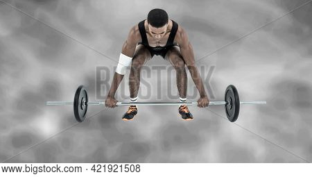 Composition of african american male weightlifter with barbell with smoke on grey background. sports and competition concept digitally generated image.