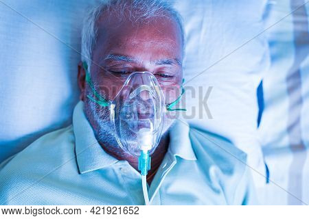 Close Up Top View Head Shot Of Old Breathing With Ventilator Oxygen Mask At Hospital Due To Coronavi