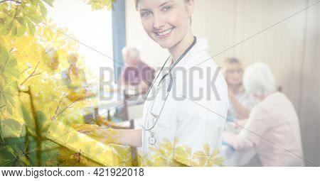 Composition of smiling female doctor anc senior people in retirement home with tree overlay. retirement and senior lifestyle concept digitally generated image.