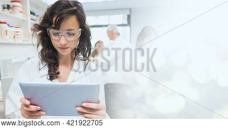 Composition of female pharmacist using tablet, with blurred copy space to right. medical and science research concept digitally generated image.