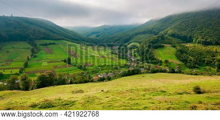 Village In The Valley Of Carpathian Mountains. Rural Landscape In Early Autumn. Fields And Pastures
