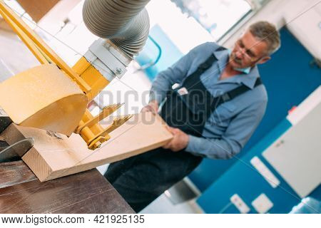 Portrait Of An Elderly Carpenter Or Carpenter In Overalls Working With Wooden Boards In A Carpenters