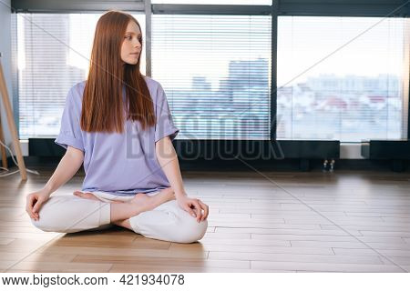 Relaxed Attractive Young Woman Meditating Sitting On Floor In Lotus Pose On Background Of Window In