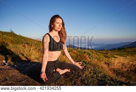 Slim Young Woman Sitting And Meditating On Fresh Air. Concept Of Yoga Time On Nature.