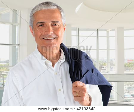 Portrait of a casually dressed businessman in a modern office building. Man is smiling holding his jacket over his shoulder.