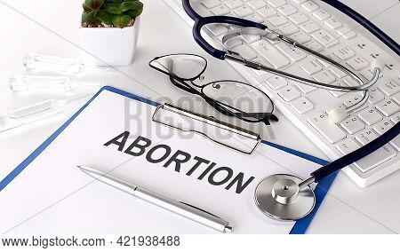Abortion Text On White Paper On The White Background. Stethoscope ,glasses And Keyboard