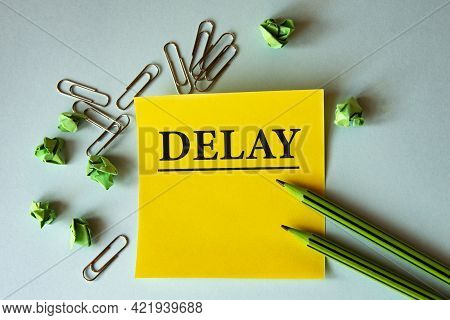 Delay - Word On A Yellow Note Paper On A Light Background With Pencils, Crumpled Pieces Of Paper And