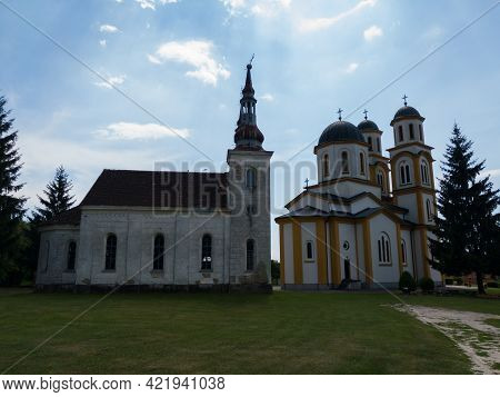 Kozarac, Bosnia And Herzegovina - August 1, 2020: The Old And New Church Of St. Peter And Paul In Ko