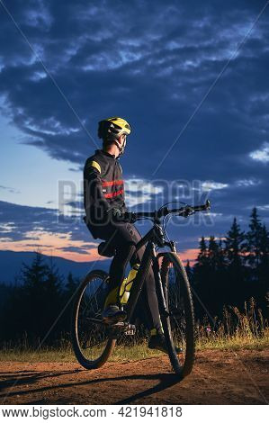 Young Man In Cycling Suit Sitting On Bicycle Under Beautiful Night Sky. Male Bicyclist In Safety Hel