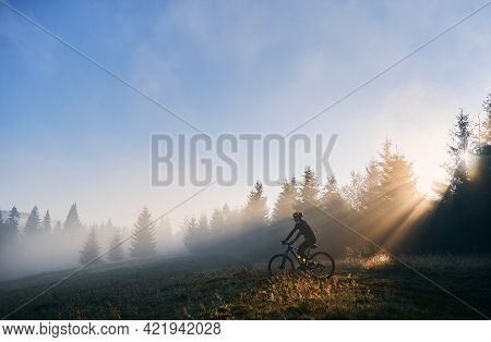 Side View Of Young Man In Cycling Suit Riding Bicycle Illuminated By Morning Sunlight. Male Bicyclis