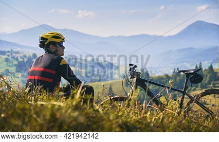 Young Man In Safety Helmet And Glasses Sitting On Grass Near Bicycle. Male Bicyclist Resting On Gras
