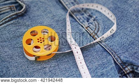 Blue Jeans And A Measuring Tape. Slimming Or Sewing Denim Concept. Measuring Tape In Yellow Spool On