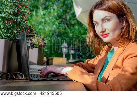 Red-haired Young Woman In A Elegant Blazer Sits On The Open Veranda Of A Cafe With A Laptop. Working