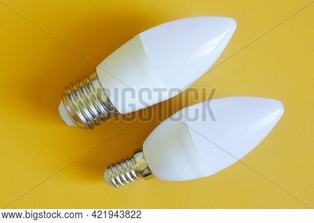 Household Led Bulbs On A Yellow Background. Comparison Of Small - E14 And Large - E27 Led Lamp Base.