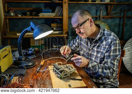 Radio Amateur Engaged In The Repair Of A Radio Receiver At Home. On The Table Are Tools For Repair