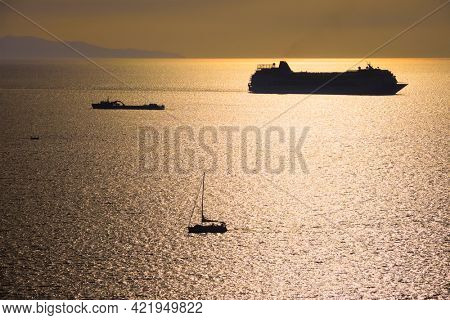 Cruise ship and yacht boat silhouettes in Aegean sea on sunset. Mykonos island, Greece