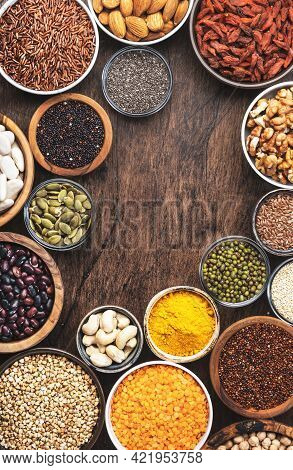 Superfoods, Legumes, Cereals, Nuts, Seeds Set In Bowls On Wooden Background. Superfood As Chia, Spir