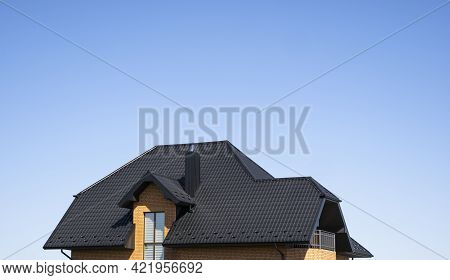 Brown Corrugated Metal Profile Roof Installed On A Modern House With A Attic Windows. The Roof Of Co