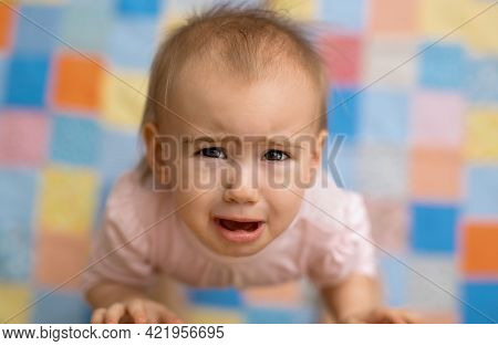 The Baby Cries Standing Next To His Mother And Looking Up. A Cute, Tearful Baby. Portrait Of A Littl