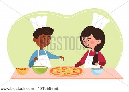 Two Smiling Little Children Are Cooking Pizza Together In A Kitchen. Little Kids Are Wearing Chefs T