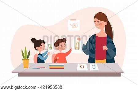 Two Little Children Are Learning Alphabet In Kindergarten With Teacher. Smiling Female School Teache