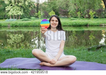 A Woman Meditates In Nature And Eats A Reusable Bubble Wrap Pop It Antistress Toy. Deal With Stress