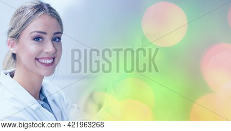 Composition of smiling female lab technicians at work, with colourful bokeh copy space to right. medical and science research concept digitally generated image.