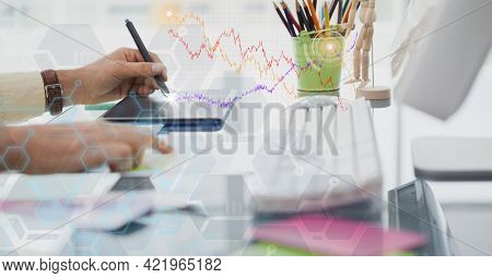 Composition of person at desk using computer and tablet with digital interface screen. global science, communication, research and digital interface concept digitally generated image.