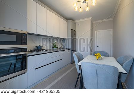 Modern simple gray and white kitchen interior with dining table