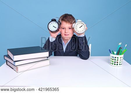 Happy Junior Boy With A Clock In His Hands Sits At A School Desk, Copy Space