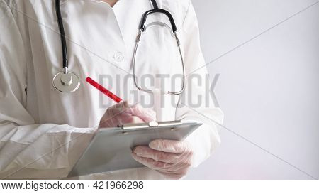 Close-up Of A Doctor Writing A Prescription In A Medical Record On A Tablet. A Doctor In A White Coa