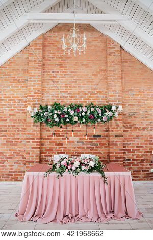 Floristic Composition Of Fresh Flowers Decorates Festive Table And Wall. Rustic Decoration Of Celebr