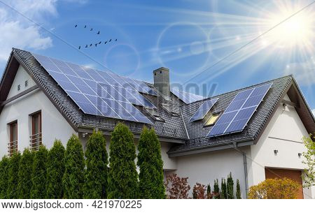 Solar Panels On A Gable Roof. Beautiful, Large Modern House And Solar Energy. Rays Of The Sun.
