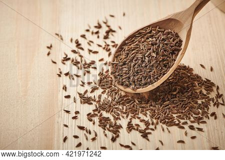 Close Up Caraway Seeds. Dried Caraway Seeds In Wooden Spoon On The Table. Pile Of Cumin Seeds. Seaso