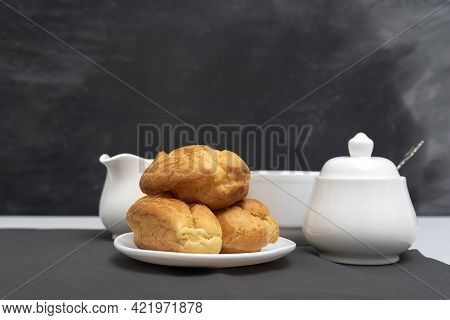 Homemade Delicate Profiteroles On Table, Cup Of Tea. Traditional French Eclairs. Gray Background.