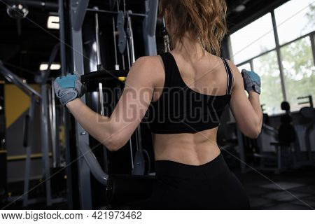 Cropped Rear View Shot Of A Sportswoman Doing Back Muscles Exercise On Lat Pull Down Gym Machine