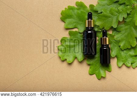 Bottle With Herb Essential Oil On Stone Background. Transparent Cosmetic Amber Glass Dropper Bottle,