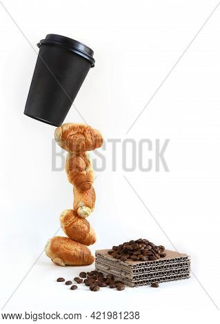 Paper Coffee Cup Levitate On A Mini-croissant Tower And A Pile Of Coffee Beans On A Piece Of Paperbo